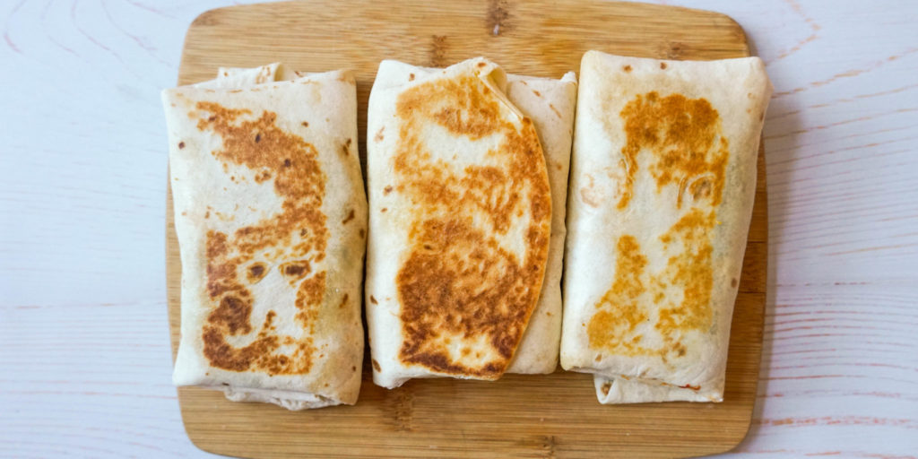 Three golden breakfast starbucks copycat recipe wraps are placed side by side on top of a brown wooden cutting board.