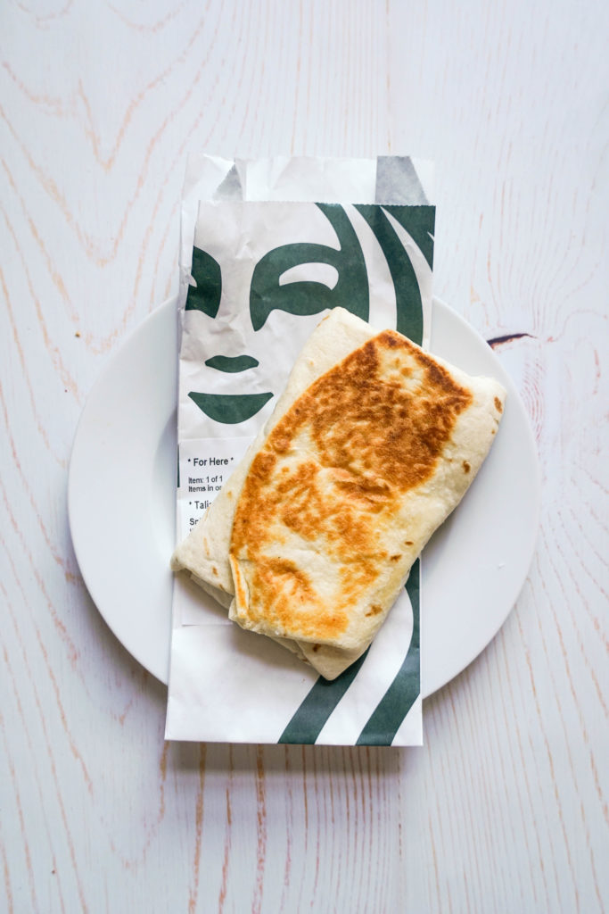 There is a golden breakfast wrap laying on top of a Starbucks wrapper, that has the company logo in green. Both are on top of a white plate