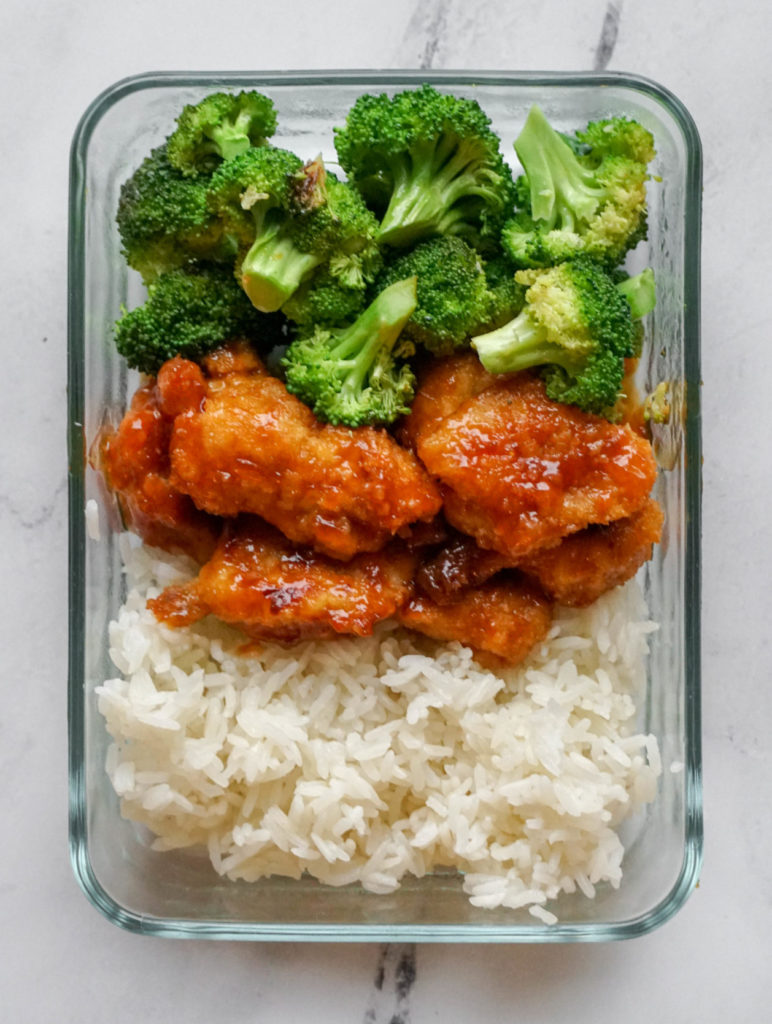 A rectangular glass container that has broccoli, orange chicken, and white rice